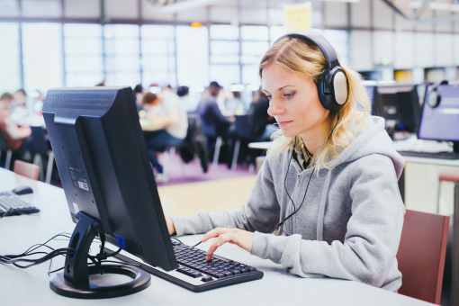 Egy nő a könyvtárban a számítógépen használja. Fejhallgatót visel.