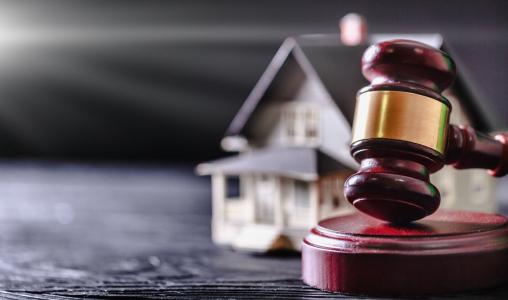 A képen egy bírói kalapács és egy családi ház makettje látható.