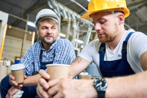 Két munkás férfi szünetet tart, kávéznak.
