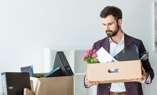 Egy férfit kirúgtak a munkahelyéről. Kezében egy doboz van a személyes holmijaival.