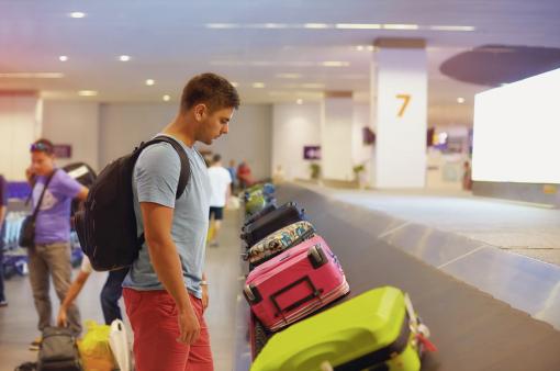 Egy fiatal férfi a reptéren a csomagját várja.