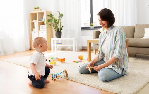 Egy anya otthon a nappaliban játszik a gyerekével.