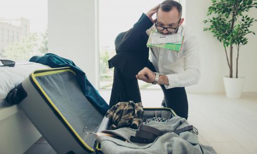 Egy férfi a bőröndjébe csomagol. Késésben van.