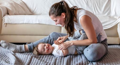 Egy fiatal anyuka játszik a down-szindrómás gyerekével a nappaliban.