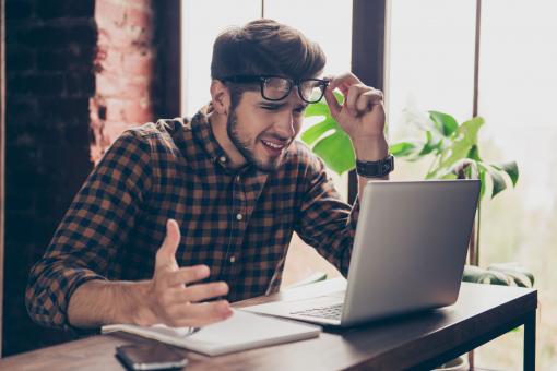 Egy fiatal férfi döbbenten bámul a laptopja képernyőjére.