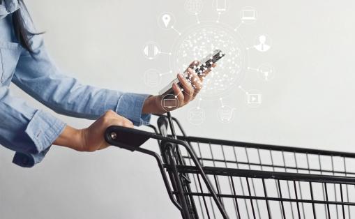 Egy nő egy bevásárlókosarat tol és okostelefont tart a kezében. Az online vásárlást szimbolizálja.