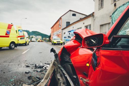 közeli kép egy összetört autóról és egy autóbalesetről. A képen egy mentőautó is látható.
