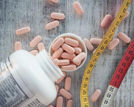 A képen egy gyógyszeres doboz, kapszulák és mérőszalag látható.