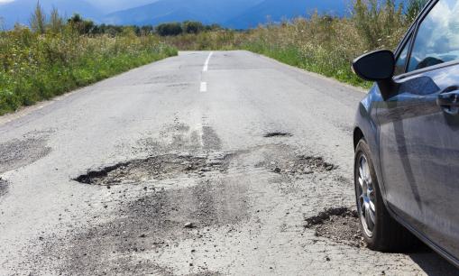 Az úton egy autó halad, az út tele van kátyúkkal.