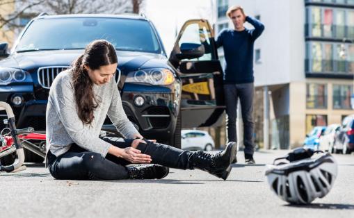 Egy biciklis balesetet szenvedett, a földön fekszik, és fáj a lába. A sofőr kiszállt az autóból.