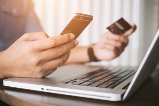Online fizetés: a képen egy laptopot, egy telefont és egy bankkártyát láthatunk, amelyet kézben tartanak.