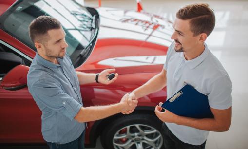 A képen egy férfi autót vásárol egy férfi kereskedőtől. A kereskedő átadja a kulcsot az új tulajdonosnak.