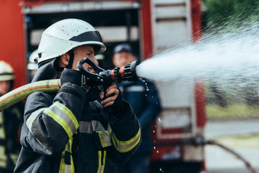Egy tűzoltó éppen tüzet olt.