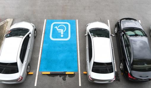 Egy parkolóban autók parkolnak, mellettük egy mozgáskorlátozottak számára fenntartott parkolóhely áll üresen.