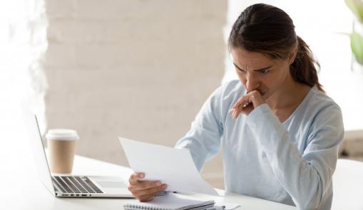 Egy fiatal nő ül az íróasztalánál és egy levelet olvas. Láthatóan rossz hírt kapott.