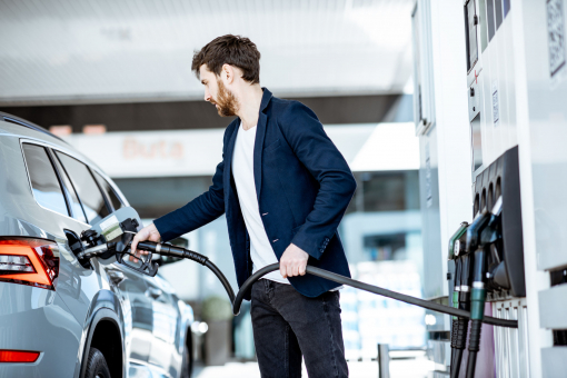 Egy fiatal öltönyös férfi tankolja az autóját.