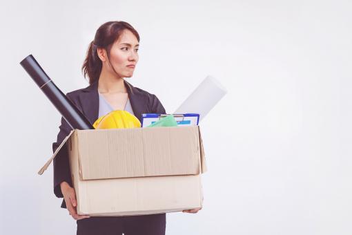 Egy fiatal nő egy tele dobozzal a kezében áll egy helyben. Távozik a munkahelyéről.