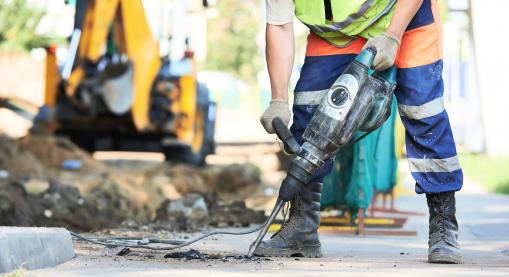 Egy munkás javítja az utat. Ütvefúróval dolgozik.
