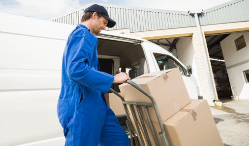 Egy férfi házhoz szállít egy nagyobb csomagot.