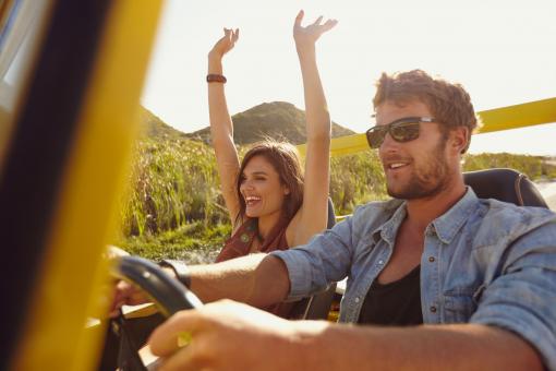 Egy fiatal pár kocsikázik a nyári napsütésben.