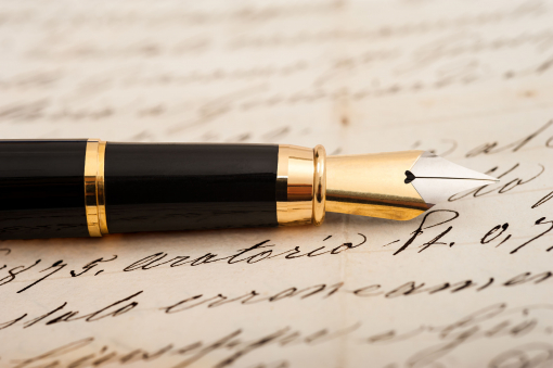 A képen egy tintás toll és egy levél található.