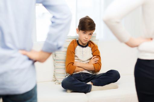 Egy szomorú gyerek ül a kanapén. A szülei csípőre tett kézzel állnak előtte.