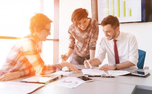 Kis vállalkozói csoport dolgozik az irodában. Két nő és egy férfi terveket készít az asztalnál.
