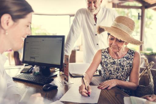 Egy hitel recepcióját látjuk. A recepciós és a vendég kitölti a papírokat.