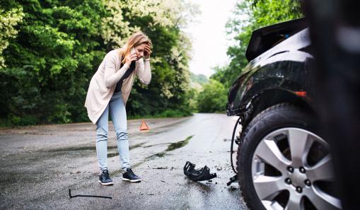 Egy fiatal nő ijedten telefonál az út szélén. Balesetet szenvedett, az autója romokban van.