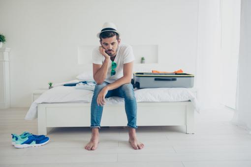 Egy fiatal férfi nyári kalapban ül az ágyon. Körülötte ott hevernek a csomagjai, ruhái. Szomorú. Valószínűleg elmarad a nyaralás.