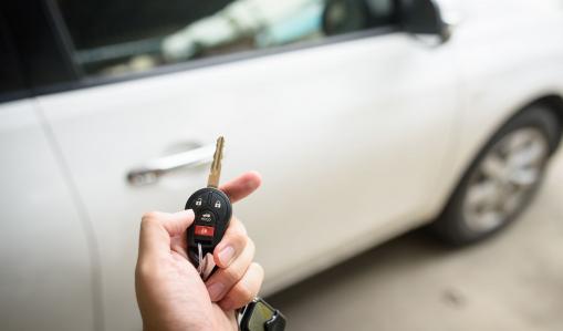 Egy férfi a kezében tart egy slusszkulcsot, vele szemben pedig ott egy fehér autó.