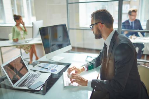 Egy üzletember ül az irodában és a laptopon dolgozik.