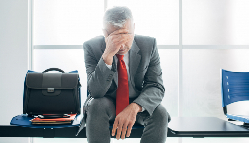 Egy szomorú öltönyös férfi ül egy váróteremben.