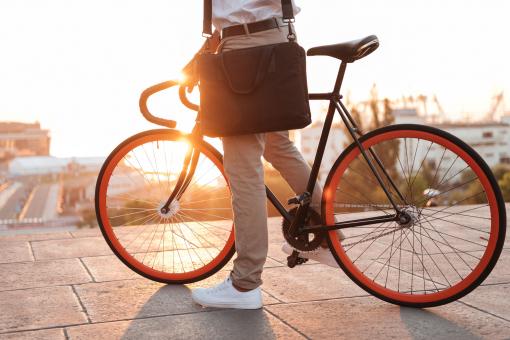 Egy fiatal férfi áll a biciklijével éppen.