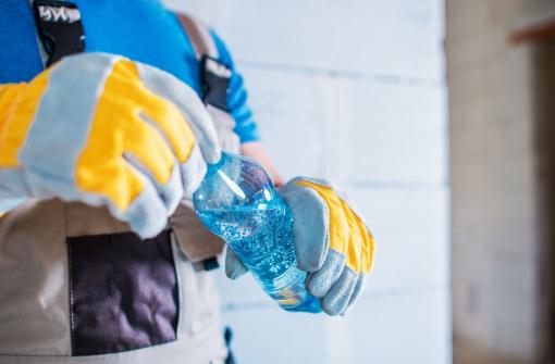 Egy munkás férfi kezében tart egy vizes palackot.