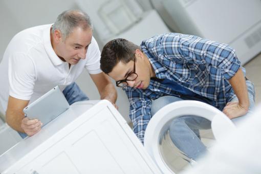 Két férfi mosógépet szerel.