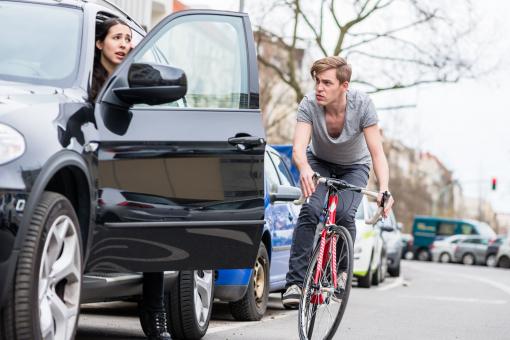 Egy autóvezető kinyitotta az autó ajtaját, és egy kerékpáros majdnem balesetet szenved miatta
