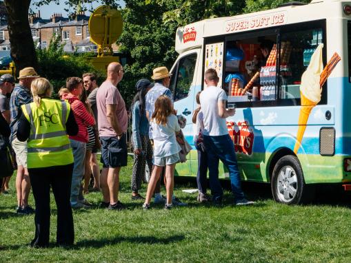 A képen egy fagylaltárus látható. Az emberek sorban állnak az autója előtt.