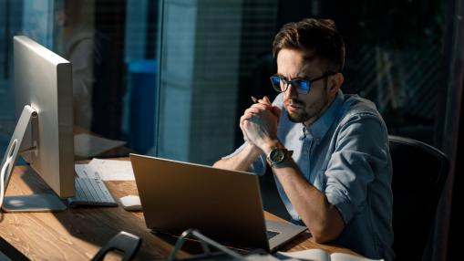 Egy fiatal férfi késő este az irodában dolgozik.