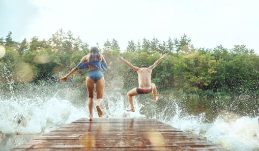 Két fiatal éppen a folyóba ugrál, és fürdőzik.