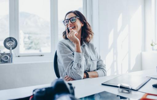 Egy fiatal szemüveges nő ül az irodában az íróasztalánál, és mosolyog