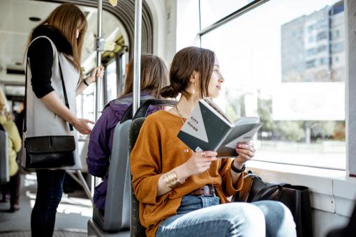 Egy fiatal nő villamoson utazik, és közben olvas.
