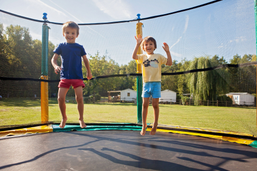 Két kisgyerek a trambulinon ugrál.