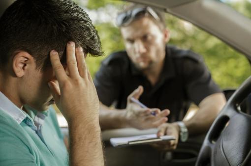 Egy rendőr igazoltat egy sofőrt.