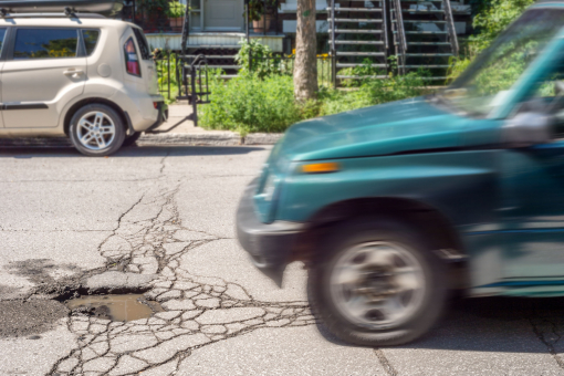A képen egy autó éppen kátyúba hajt.