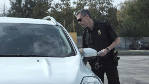 Egy rendőr megállított egy sofőrt, és igazoltatja.