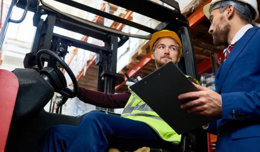 Két férfi munkavédelmi sisakban beszélget egy raktárban.