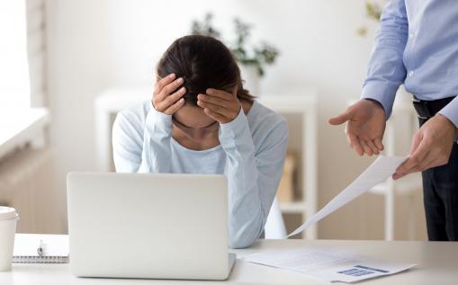 Az irodában a laptop előtt egy fiatal nő ül, mellette a főnöke egy iratot mutat felé felháborodva.