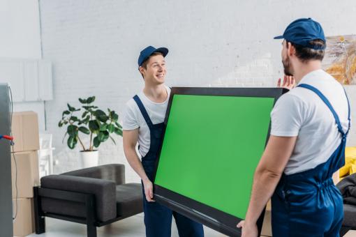 Két költöztető férfi elvisz egy tévét.