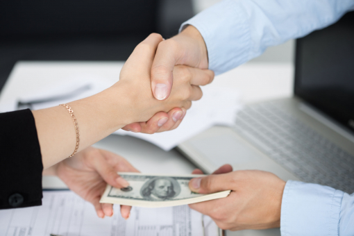 Kézfogás - egy férfi és egy nő kezet fognak. A nő pénzt ad a férfinak.
